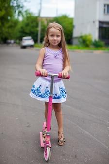 Mode schattig klein meisje op een scooter in de straat