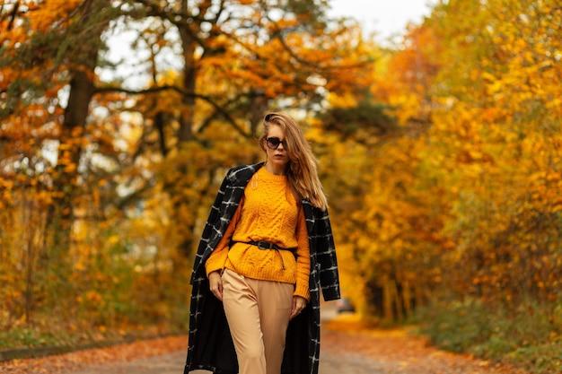 Mode schoonheid blanke vrouw in stijlvolle herfstkleding met vintage gebreide trui en zwarte jas loopt in het park met verbazingwekkende kleurrijke bomen en herfstbladeren.