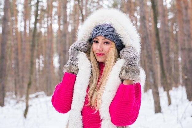 Mode, schoonheid en mensen concept - portret van blonde jonge vrouw in bontjas op winter achtergrond