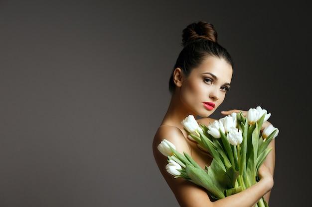 Mode shot van glamoureuze jonge vrouw met een boeket van een witte tulpen. studio opname over een grijze achtergrond. lege ruimte