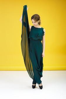 Mode shot van mooie vrouw in groene jurk op een gele achtergrond