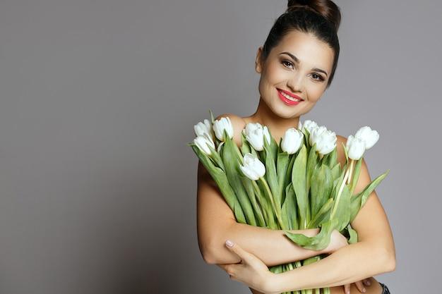 Mode shot van vrolijke jonge vrouw met een boeket van een witte tulpen. studio opname over een grijze achtergrond. lege ruimte