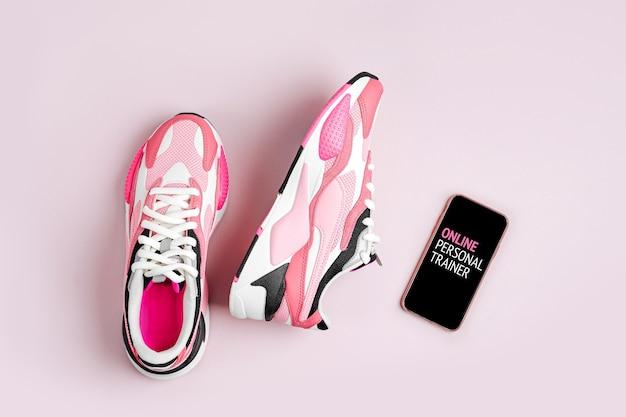 Mode sneakers met smartphone op een roze achtergrond. app om binnen te trainen.