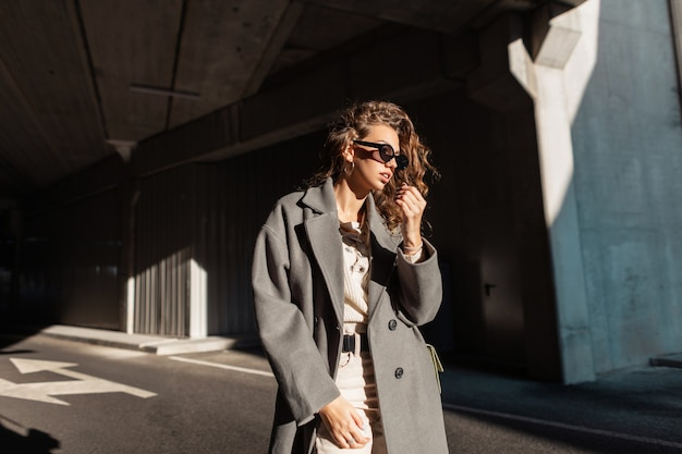 Mode stedelijk portret van stijlvolle mooie krullende vrouw met zonnebril in vintage casual lange jas loopt op straat