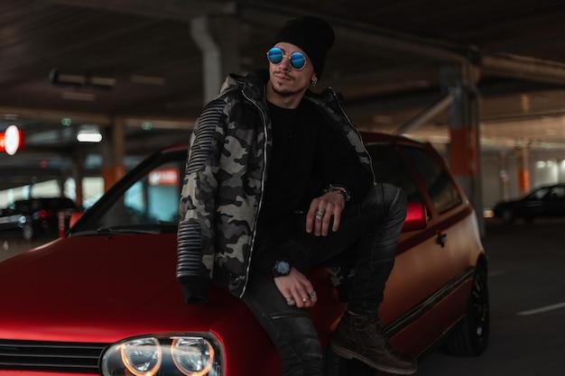 Mode stedelijke man model met zonnebril en hoed in stijlvolle militaire winterjas en pullover staat in de buurt van een rode auto op parkeerplaats