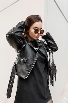 Mode stedelijke portret van een mooie vrouw in zwarte rock stijl met stijlvolle zonnebril over grijze achtergrond. schoonheid en casual vrouwelijke stijl