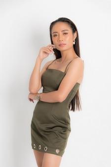 Mode-stijl catalogus casual kleding voor feest sexy mooie vrouw zwart lang haar natuurlijke make-up dragen groene jurk kostuum perfecte lichaamsvorm pak bij studio shoot op witte achtergrond en schaduw.