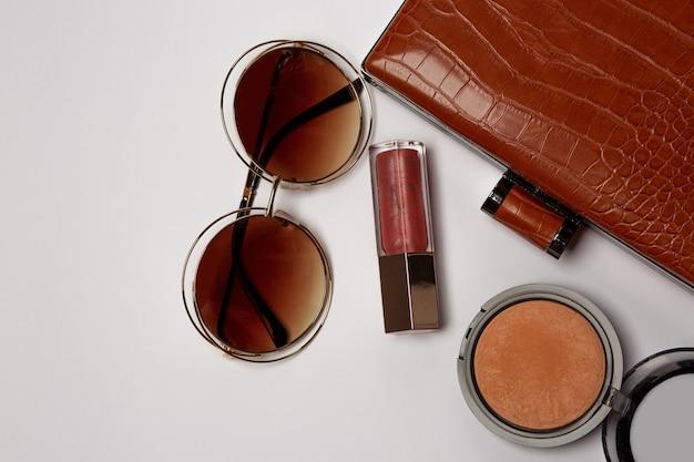 Mode stijl concept: vrouw clutch tas met poeder bronzer, zonnebril en lipgloss uitvallen op een grijze achtergrond. ruimte voor tekst
