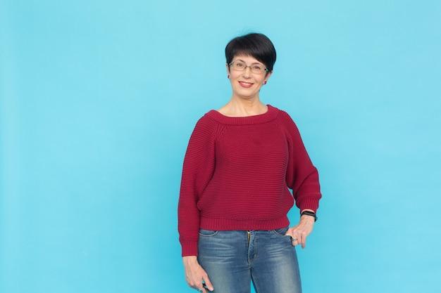 Mode, stijl en mensenconcept - mooie vrouw van middelbare leeftijd over turkooise achtergrond met exemplaar