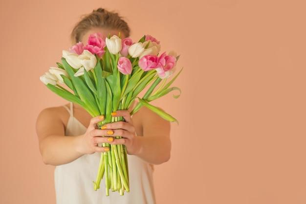 Mode stijl foto van mooi meisje in witte jurk met tulpen.
