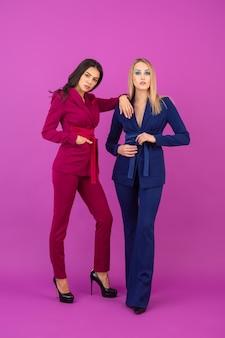 Mode-stijl twee lachende aantrekkelijke vrouwen op violette muur in stijlvolle kleurrijke avondpakken van paarse en blauwe kleur, lente modetrend