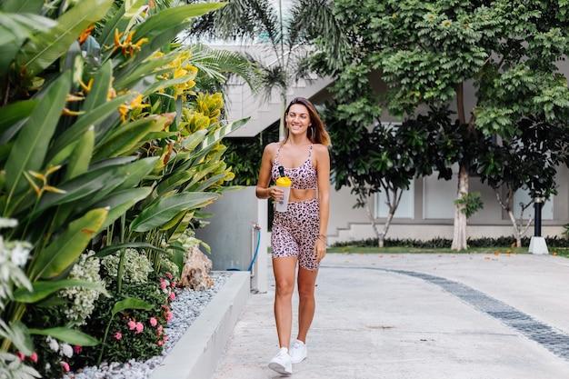 Mode stijlvolle jonge kaukasische fit sportieve vrouw in luipaard cami top en biker shorts buiten houdt eiwit shaker, fles water, in de hand