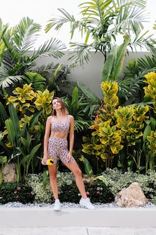 Mode stijlvolle jonge kaukasische fit sportieve vrouw in luipaard cami top en biker shorts buiten houdt proteïne shaker