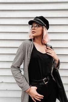 Mode stijlvolle jonge vrouw in modieuze bril en een pet met een geruit hemd, zwarte jeans en een t-shirt met een tas staat in de buurt van een houten huis