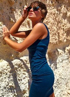 Mode stijlvolle mooie jonge brunette vrouw model in zomer blauwe jurk poseren in de buurt van zandrotsen