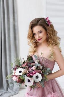 Mode studio foto van mooi jong meisje met lang krullend haar in een roze jurk en bruiloft bloemen.