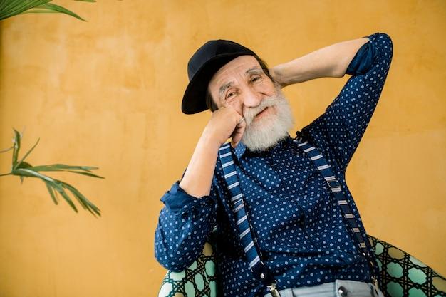 Mode studio portret van gelukkig stijlvolle 70-jarige man in zwarte pet, zittend op kleurrijke stoel op gele achtergrond, die zich voordeed op camera met aangename glimlach