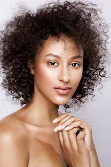Mode studio portret van mooie afro-amerikaanse vrouw met perfect gladde gloeiende mulat huid, make-up