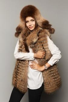 Mode studio portret van mooie dame in bontvest en pluizige bontmuts. winterschoonheid met perfecte make-up in luxe outfit geïsoleerd op een grijze achtergrond.
