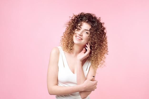 Mode studio portret van mooie lachende vrouw met afro krullen kapsel geïsoleerd