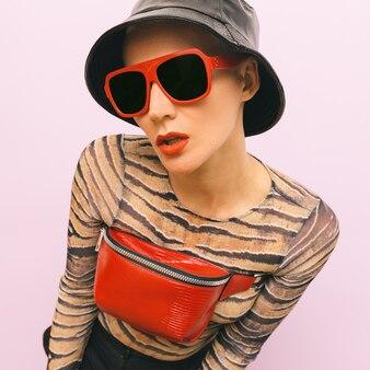 Mode swag-model. stijlvolle rode accessoires. zonnebril, clutch en hipster panama pet