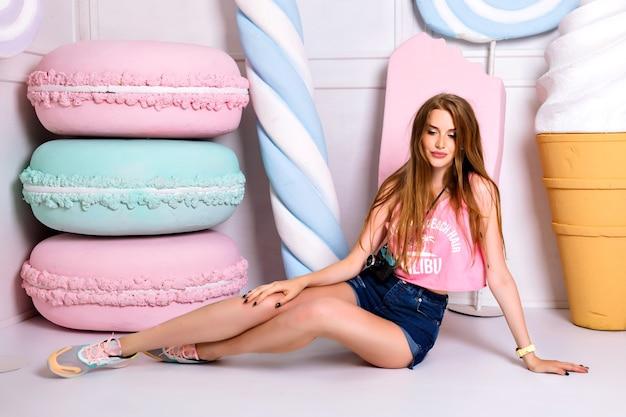 Mode trendy foto van aantrekkelijke prachtige vrouw in heldere zomerkleding, zittend op de vloer voor kleurrijke rekwisieten snoep. lang blond haar. grote sensuele lippen. raadselachtige glimlach.