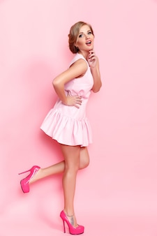 Mode van een mooie jonge vrouw in een mooie jurk die zich voordeed over roze. mode