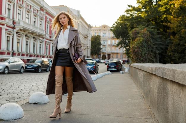 Mode volledige lengte afbeelding van elegante blonde vrouw in stijlvolle luxe beige leren jas en hoge hakken, buiten wandelen