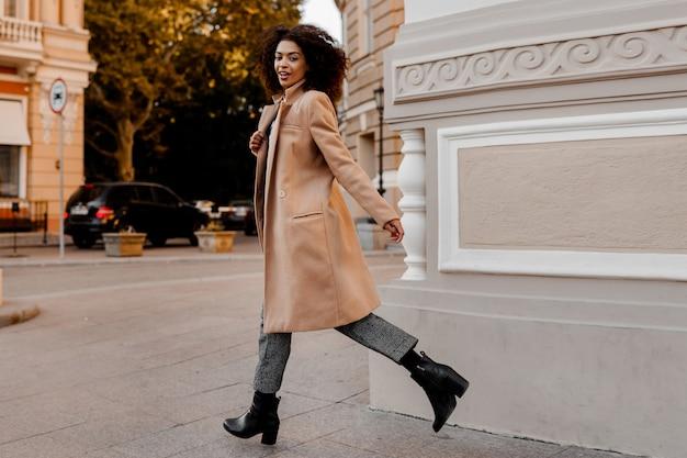 Mode volledige lengte afbeelding van elegante zwarte vrouw in stijlvolle luxe beige jas en fluwelen trui