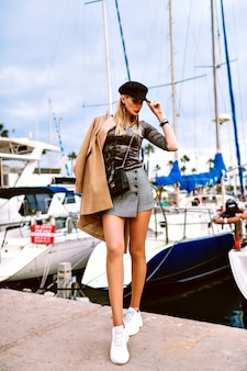 Mode volledige lengte afbeelding van vrouw poseren op straat in de buurt van jachthaven met jachten, moderne glamour trendy outfit, luxe vakantie, lente herfst tijd. sexy model poseren op straat.