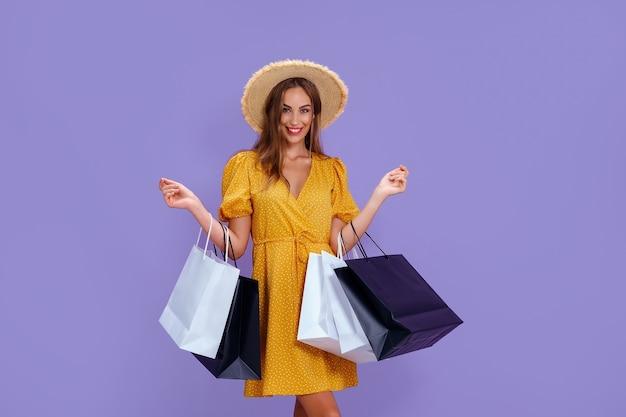 Mode volwassen meisje houdt boodschappentassen op lila achtergrond verkoop aankopen winkelen zwarte vrijdag