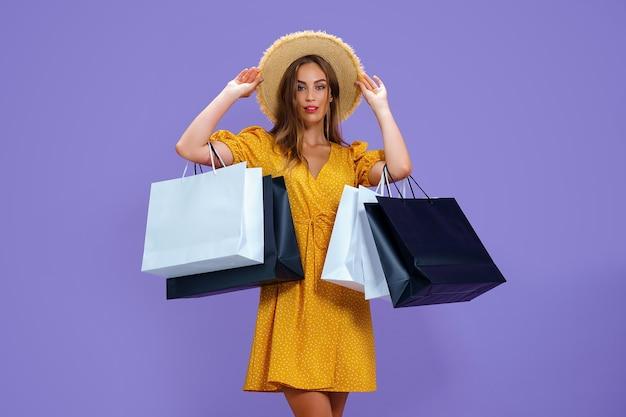 Mode volwassen meisje houdt boodschappentassen op paarse achtergrond verkoop aankopen winkelen zwarte vrijdag