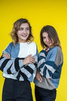 Mode vriendinnen dragen moderne gebreide trui poseren op gele muur als achtergrond.