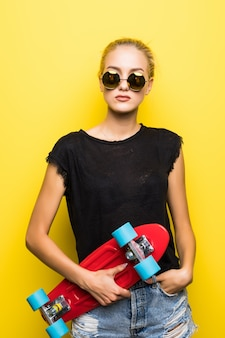 Mode vrij cool meisje in zonnebril met skateboard over kleurrijke gele achtergrond
