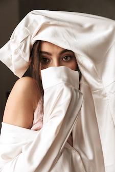 Mode vrouw camera kijken, terwijl het bedekken van gezicht met kleding binnen