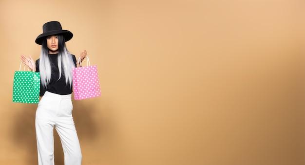 Mode vrouw greep winkelen grijze tassen, modieuze haarstijl aziatisch meisje met zwarte hoed witte broek gooien roze groene tassen