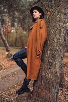 Mode vrouw in bruine jas en rode hoed poseren in het bos