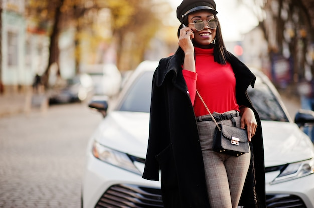Mode vrouw in jas, krantenverkoper cap en zonnebril gesteld op straat tegen witte zakelijke auto.