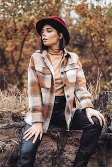 Mode vrouw in landelijke stijl zittend op de rots van de canyon