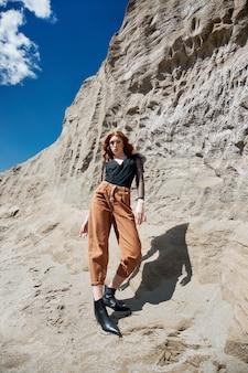 Mode vrouw in oranje spijkerbroek poseren in de natuur