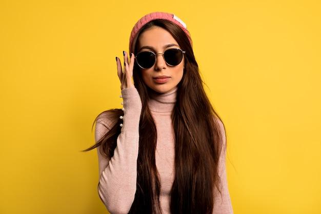 Mode vrouw in trendy kleding roze pet en ronde zonnebril dragen