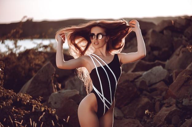 Mode vrouw in zwarte badmode liggend op tropisch strand.
