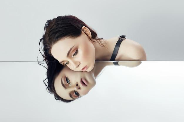 Mode vrouw ligt op spiegel en kijkt reflectie