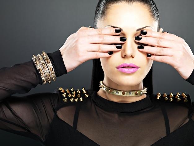 Mode vrouw met zwarte nagels en felroze lippen. stijlvol meisje met armbanddoornen in de nek
