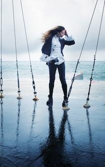 Mode vrouw poseren buiten in de buurt van de oceaan in winderige dag