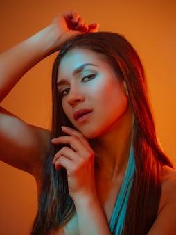 Mode vrouwelijk portret met blauwgroen neon op oranje