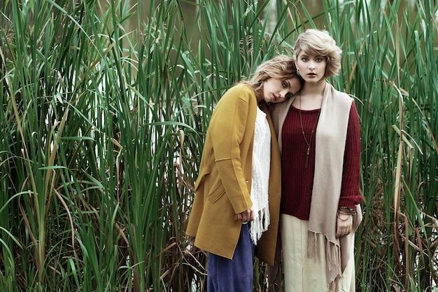 Mode vrouwen poseren samen buiten, herfst park.