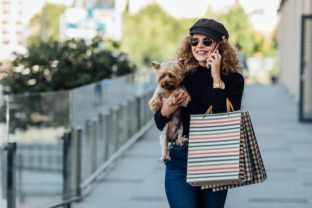 Mode wandeling vrouw met lang krullend haar houdt kleine hond en boodschappentassen mooi meisje knuffels hondje glimlachende aantrekkelijke vrouw met yorkshire terrier meisje met hond in handen en verkoop concept