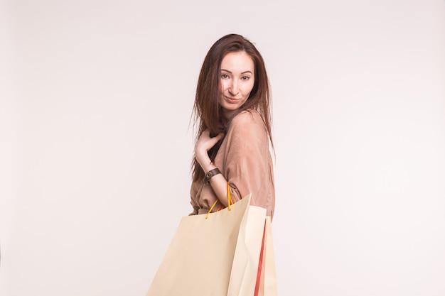 Mode-, winkel- en mensenconcept. gelukkig brunette vrouw met paperbags na het winkelen op wit met kopie ruimte