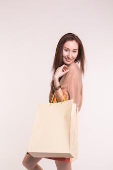 Mode-, winkel- en mensenconcept. gelukkig brunette vrouw met paperbags na het winkelen.